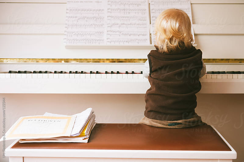 Toddler plays piano by Urs Siedentop & Co for Stocksy United