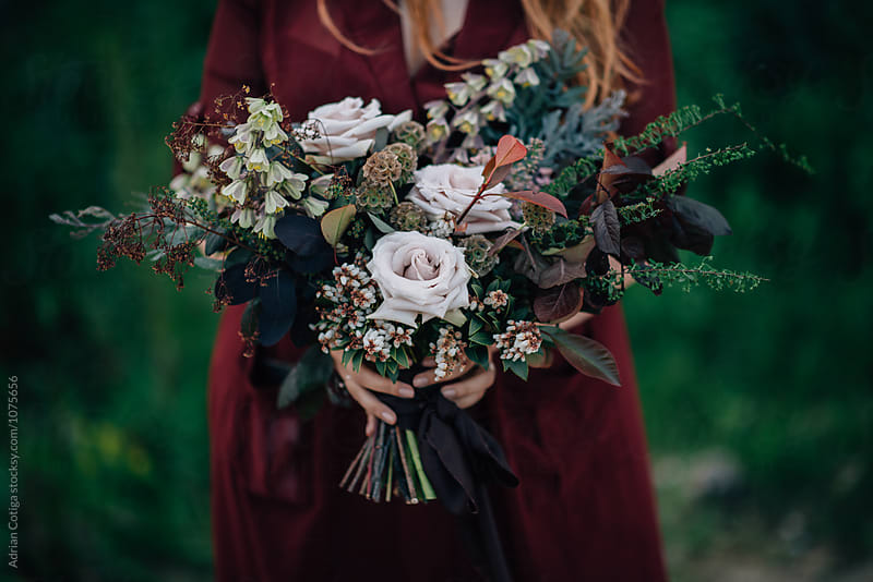 Woman holding beautiful flowers bouquet by Adrian Cotiga for Stocksy United