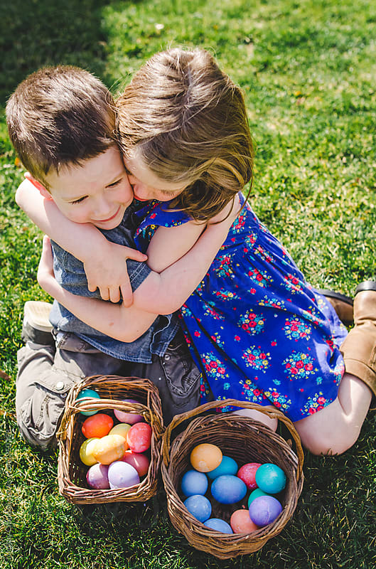 Two children hugging with Easter baskets by Lindsay Crandall for Stocksy United