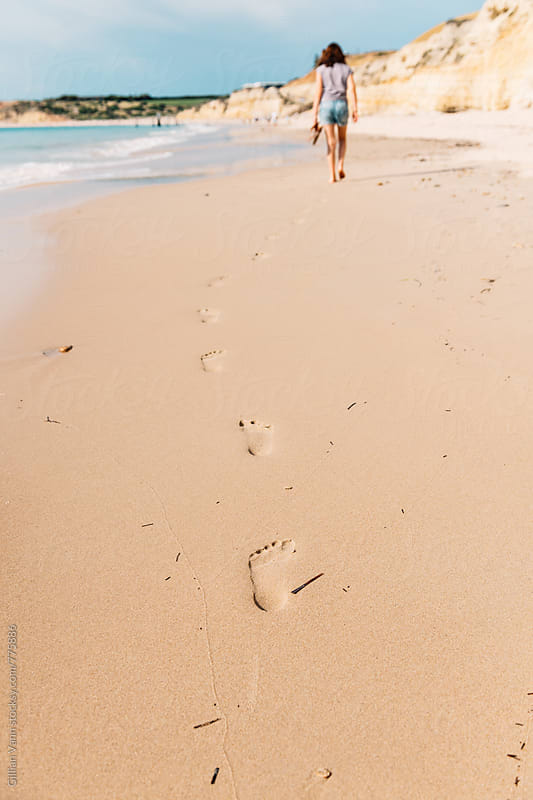 footprints on the beach, teenager in the distance by Gillian Vann for Stocksy United