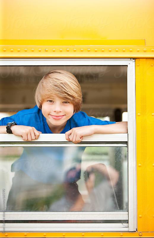 School Bus: Schoolboy Hangs out Bus Window by Sean Locke for Stocksy United