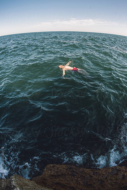 swimmer floating on the water  by RG&B Images for Stocksy United