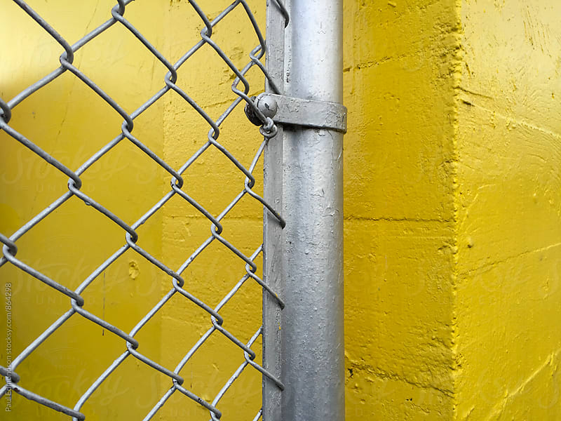 Chain-link fence and painted yellow wall, close up by Paul Edmondson for Stocksy United
