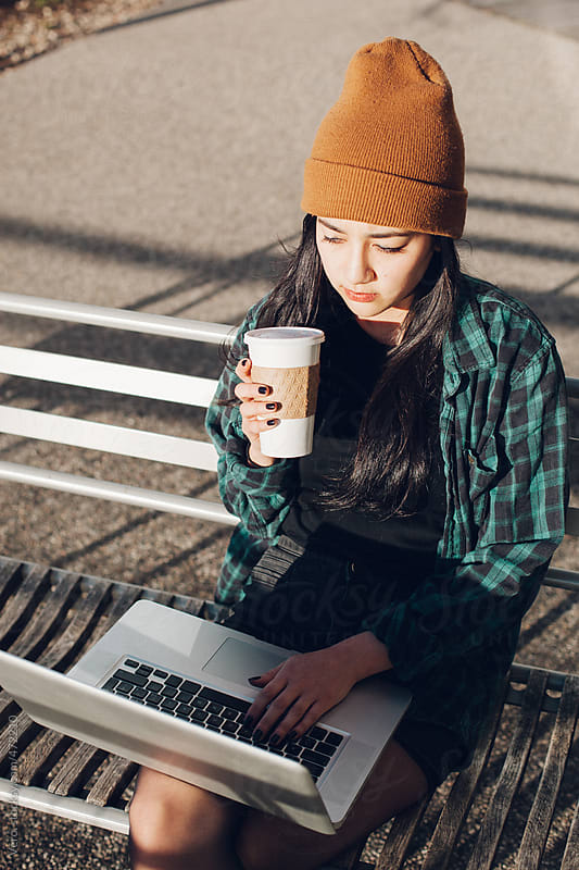 Woman working on a laptop outdoors by Good Vibrations Images for Stocksy United