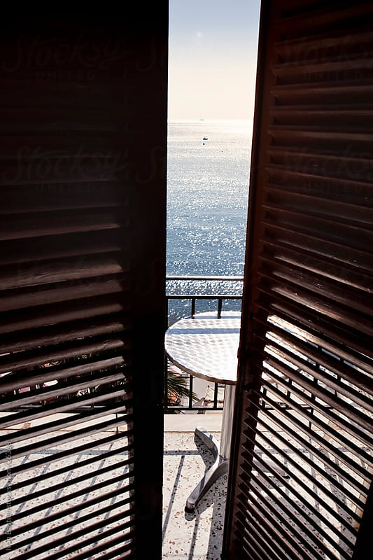 Open shutters on a hotel balcony in Greece by Ivan Bastien for Stocksy United