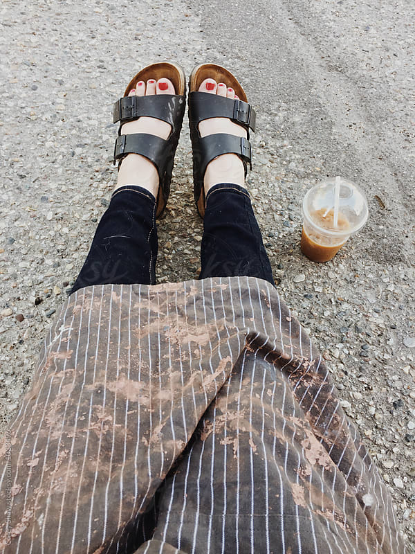 Artist wearing clay covered apron, sitting with an iced coffee by Carey Shaw for Stocksy United
