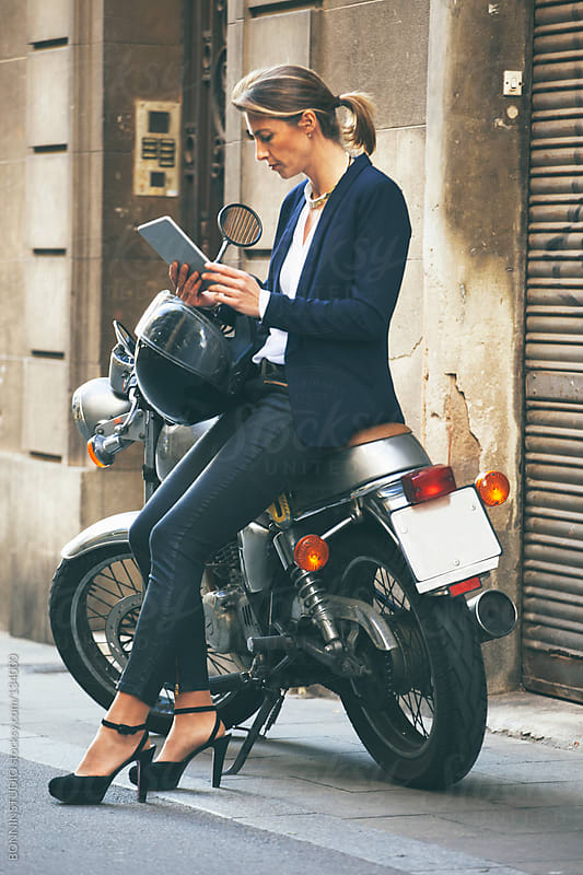 Mature business woman with digital tablet and helmet on motorbike. Urban street. by BONNINSTUDIO for Stocksy United