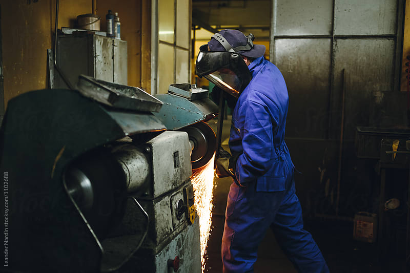 metal worker with protection mask grinding metal plate by Leander Nardin for Stocksy United