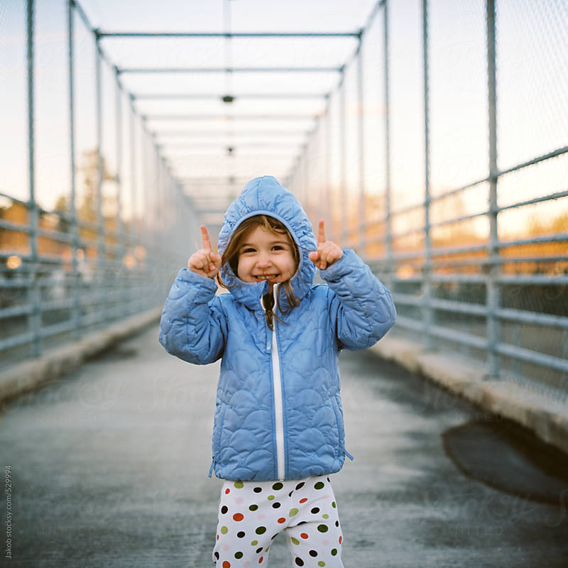 Cute and goofy toddler with a hoodie standing on an overpass by Jakob for Stocksy United