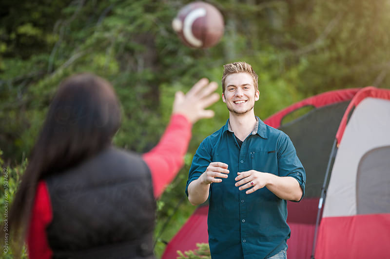Camping Couple Playing Catch With Football Near Tent by Odyssey Stock for Stocksy United