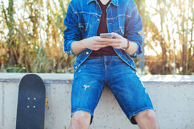 Skater young man using smartphone in a skatepark by BONNINSTUDIO for Stocksy United
