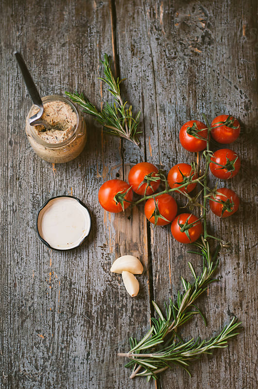Cherry tomato, rosemary and mustard on wooden table by Branislav Jovanovic for Stocksy United