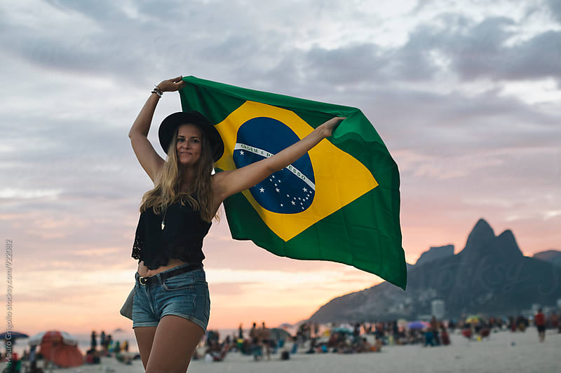 Rio de Janeiro. Brazil. Woman playing with a brazilian flag on the beach at sunset by Mauro Grigollo for Stocksy United