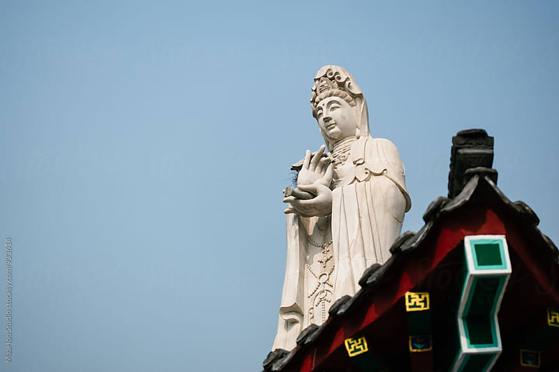 Low Angle View Of Buddha Statue Against The Sky by Maa Hoo for Stocksy United
