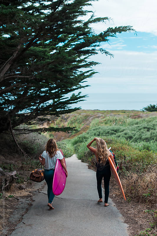 Two Female Friends Carry Surfboards Along a Path towards the Ocean by Briana Morrison for Stocksy United