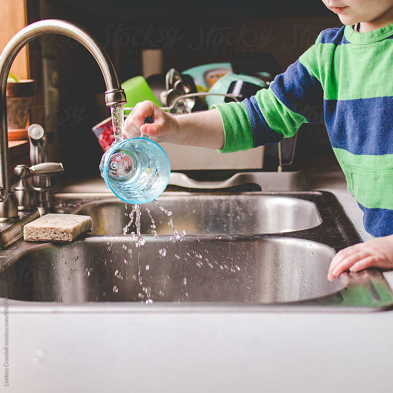 Boy playing with cup and water at the kitchen sink by Lindsay Crandall for Stocksy United
