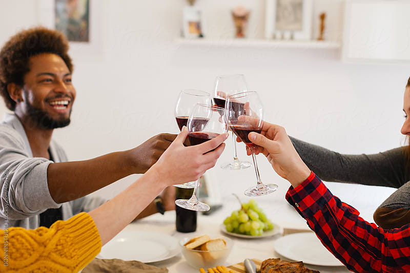 African american young man making a toast with their friends at home. by BONNINSTUDIO for Stocksy United