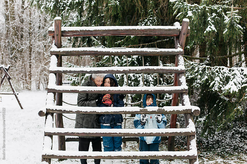 Grandma with grandkids behind the snow-covered jungle gym by Beatrix Boros for Stocksy United