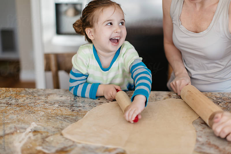 Mother showing toddler how to roll dough using a rolling pin by Jakob for Stocksy United