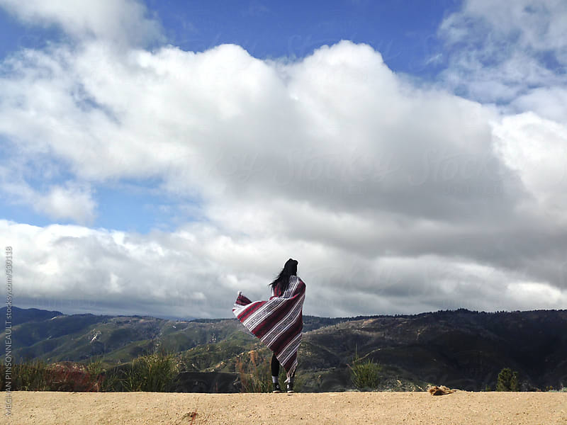 Woman with Blowing Blanket with Mountains and Sky by MEGHAN PINSONNEAULT for Stocksy United