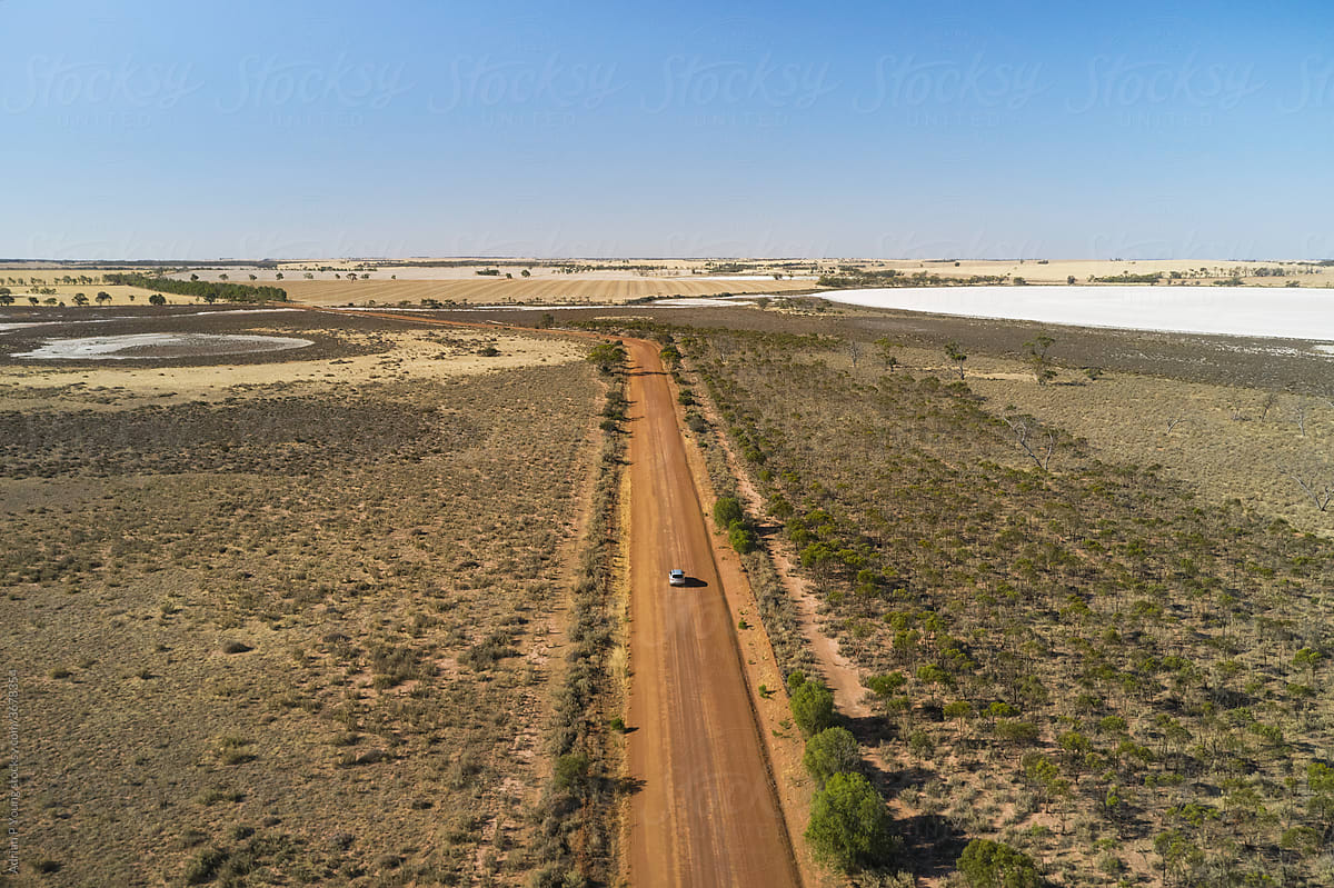 Small SUV On Rural Road Through Dry Salt Lake
