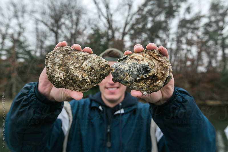 Man holding oysters by Matthew Spaulding for Stocksy United