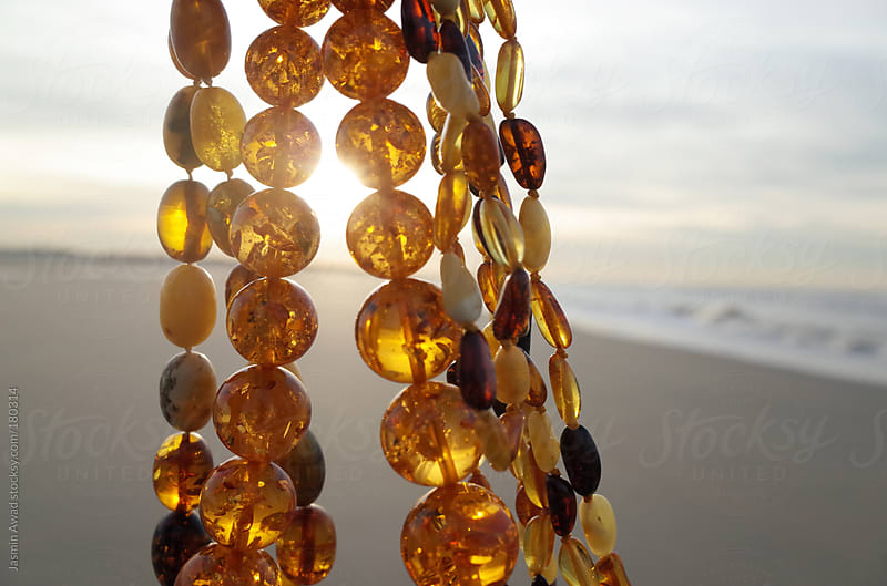 Amber Jewelry with sunlight at the beach by Jasmin Awad for Stocksy United
