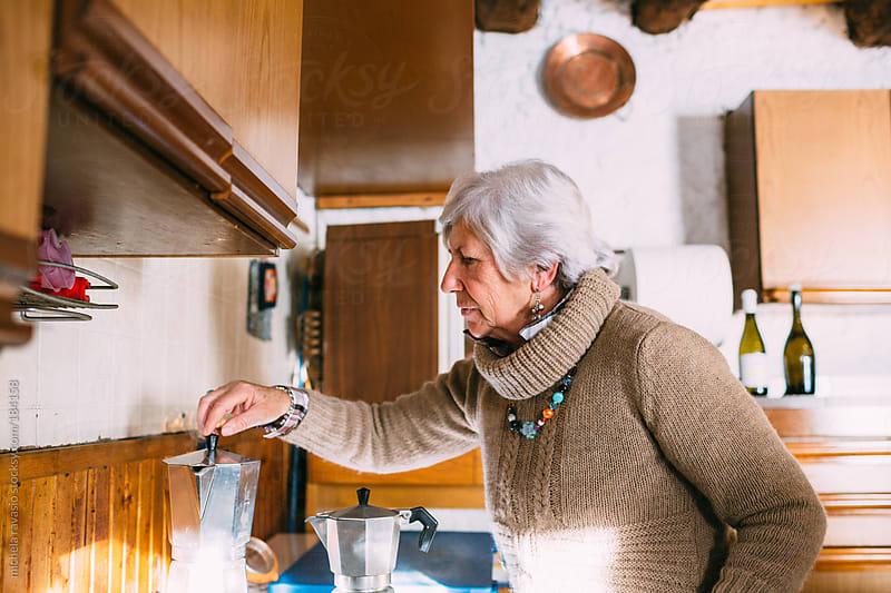 An elderly woman preparing coffee by michela ravasio for Stocksy United
