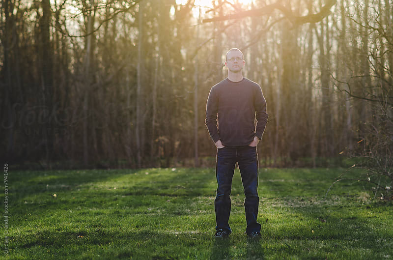 Man standing outside of woods at sunset by Lindsay Crandall for Stocksy United