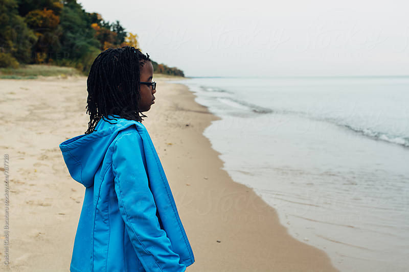 Black girl in blue coat standing on a beach by Gabriel (Gabi) Bucataru for Stocksy United