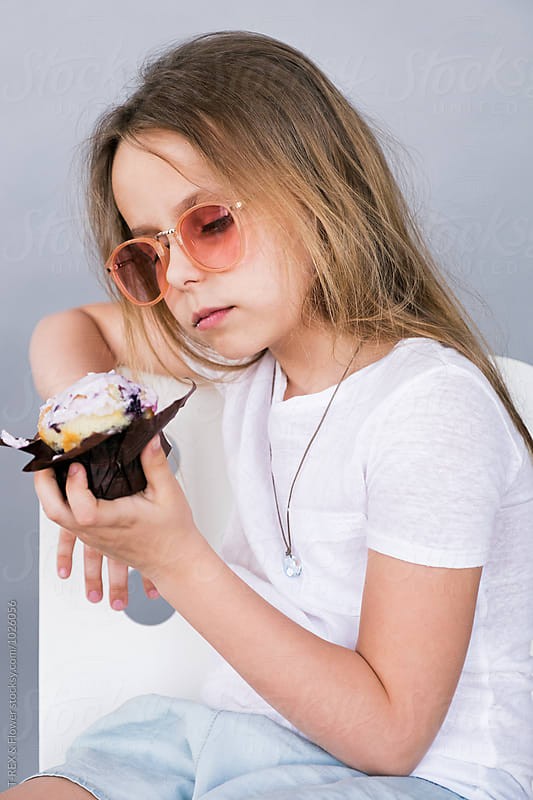 Girl in sunglasses looking at dessert by Danil Nevsky for Stocksy United