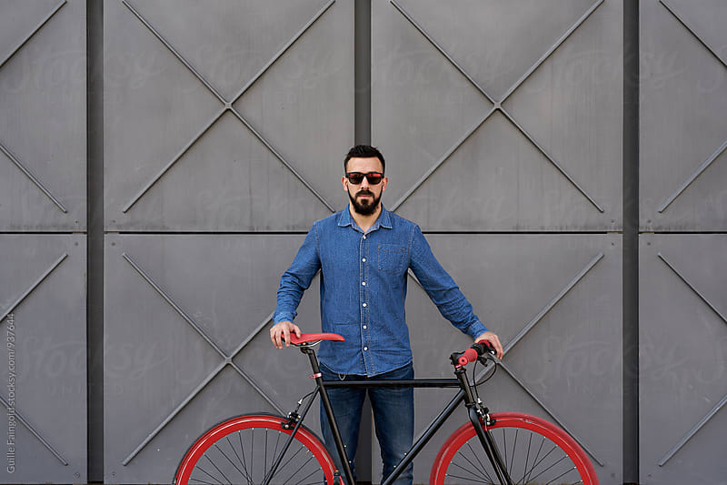 Portrait of young man with fixed gear bicycle by Guille Faingold for Stocksy United