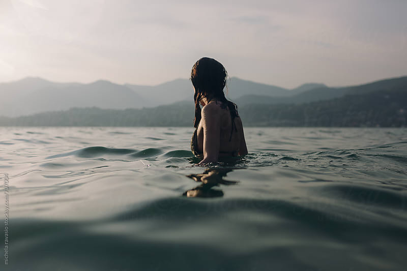 Woman in the lake at sunset by michela ravasio for Stocksy United
