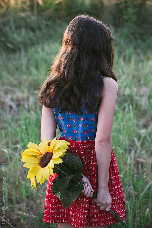 Portrait of a young girl with sunflower from back by Evil Pixels Photography for Stocksy United