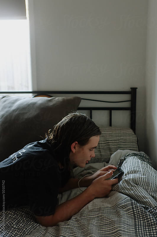 Teen boy on phone on bed by skye torossian for Stocksy United