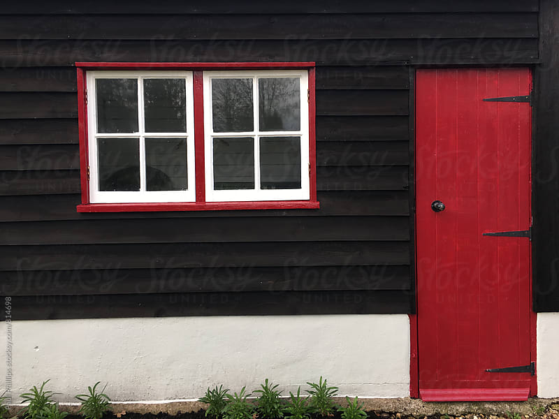 Outbuilding with red door and window frames. by Paul Phillips for Stocksy United