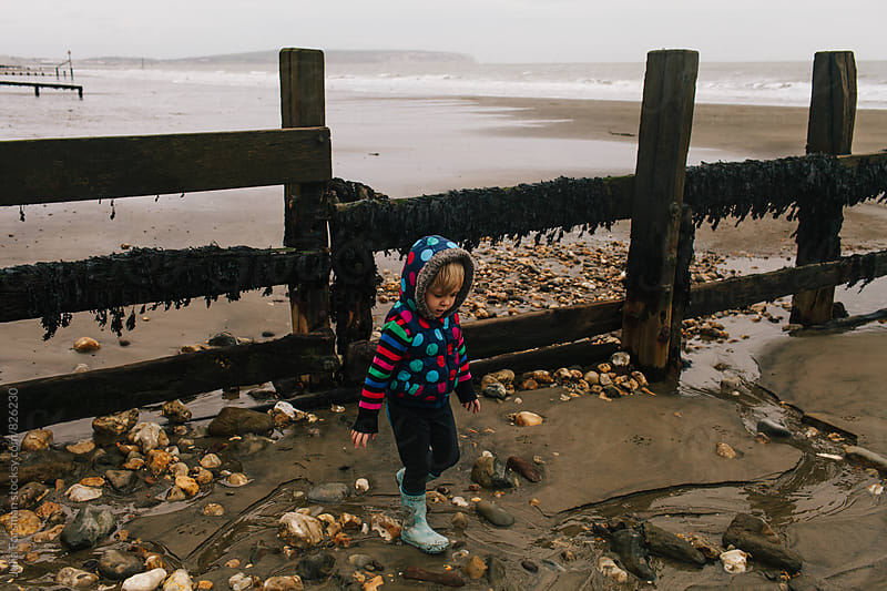 Small child walks on pebbles next to a sea barrier on a sandy beach in winter. by Julia Forsman for Stocksy United