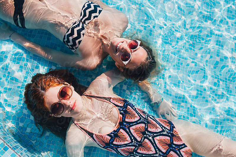 Girls Lying in the Swimming Pool by Lumina for Stocksy United
