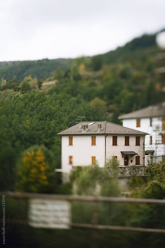 Blurred sight of building amongst trees on northern italy mountain by Laura Stolfi for Stocksy United