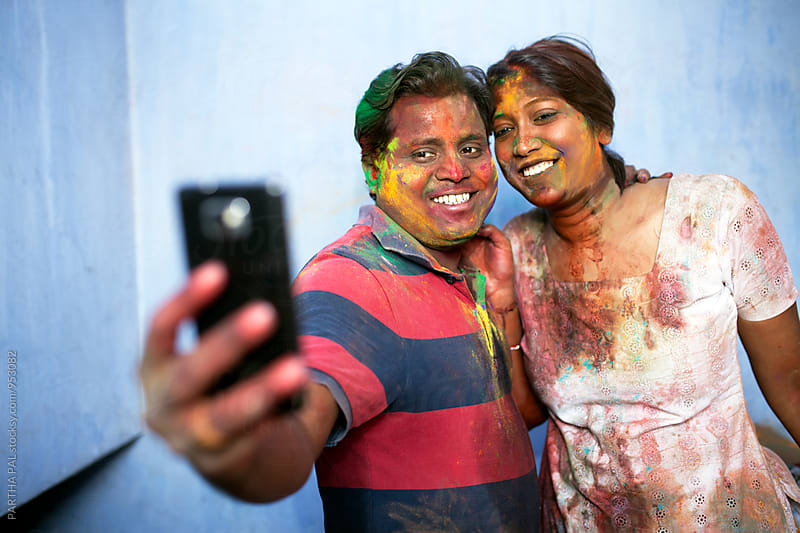 couple smudged with colorful powder on  face and shooting selfie by PARTHA PAL for Stocksy United