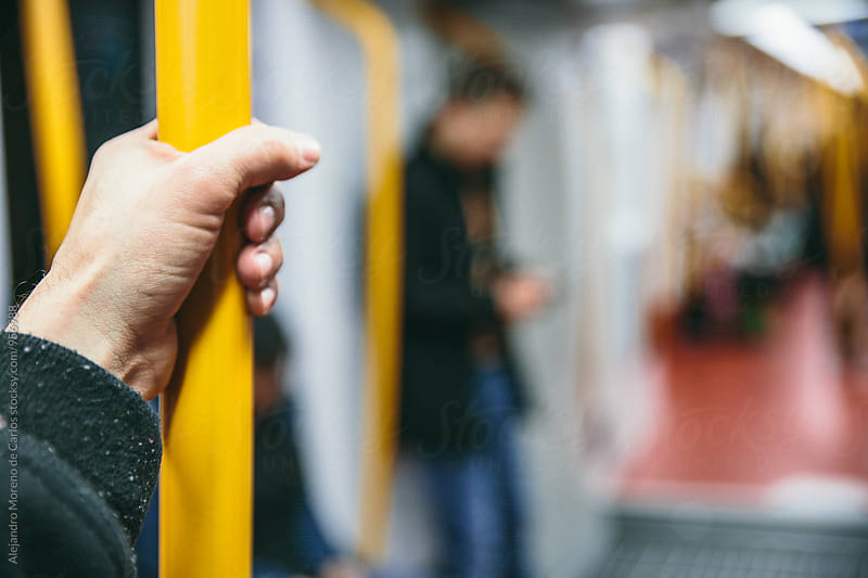 Hand of a passenger holding onto subway bar while traveling on the subway train by Alejandro Moreno de Carlos for Stocksy United