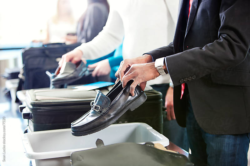 Airport: Man Puts Shoes in Security Bin by Sean Locke for Stocksy United