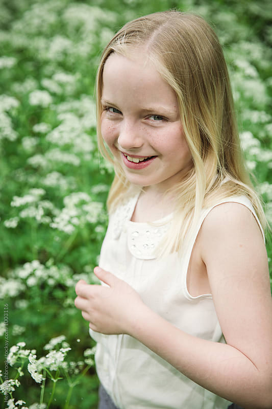 A smiling little girl outdoors by Helen Rushbrook for Stocksy United