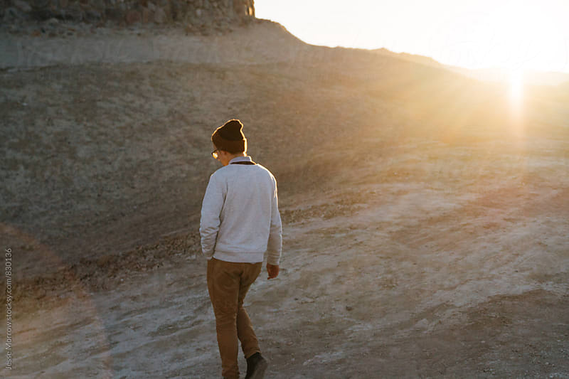 young male wearing white stylish sweater walking outdoors at sunrise in desert by Jesse Morrow for Stocksy United