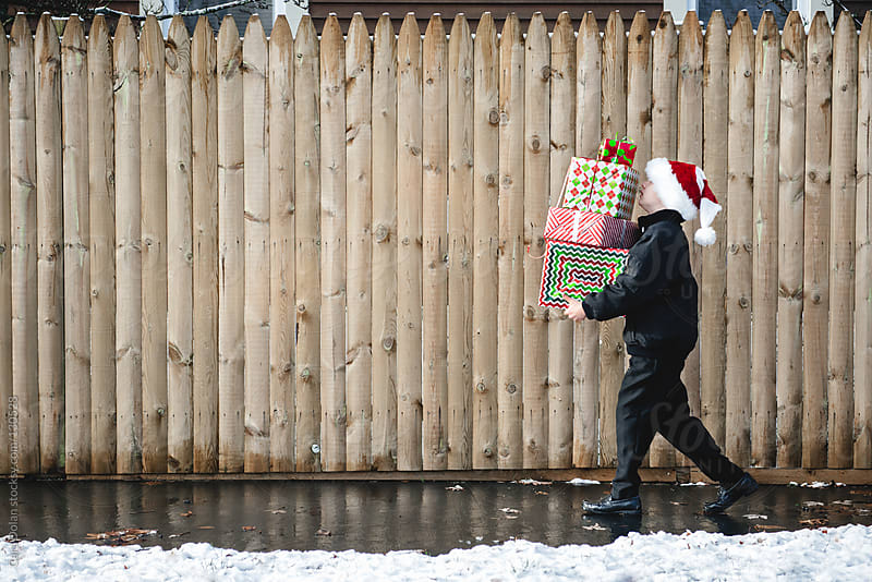 Boy wearing Santa hat carries a stack of Christmas presents  by Cara Dolan for Stocksy United
