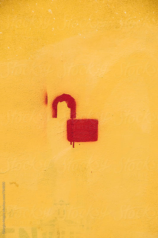 Unlocked Lock Stencil Graffiti on Yellow Plaster Wall by Giorgio Magini for Stocksy United