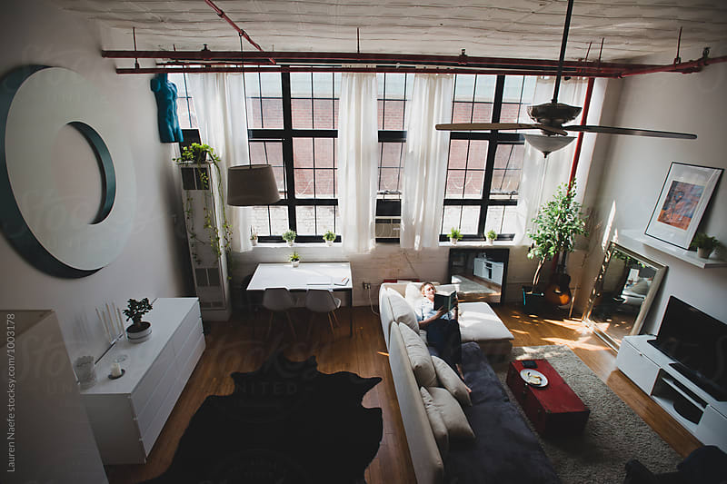 Young woman in loft apartment by Lauren Naefe for Stocksy United