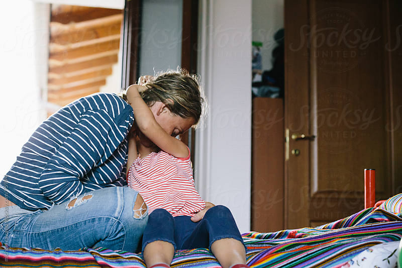 Little girl hugs her pregnant mother by michela ravasio for Stocksy United