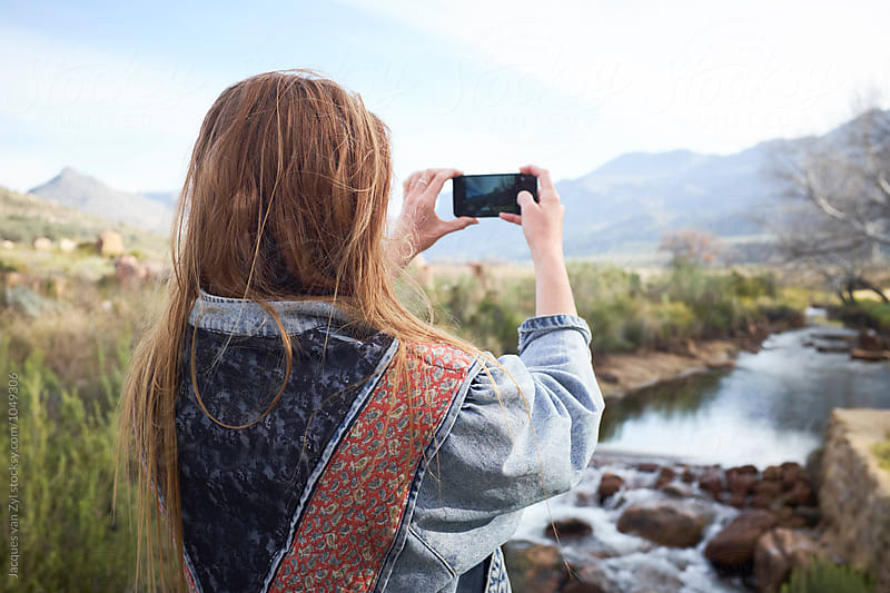 She take a photo of a river. by Jacques van Zyl for Stocksy United
