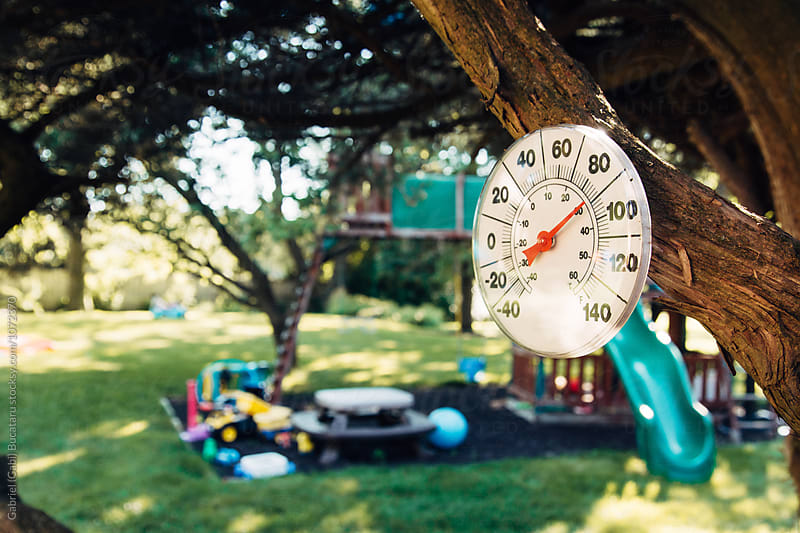 Summer temperature on an outdoor weather thermomether by Gabriel (Gabi) Bucataru for Stocksy United